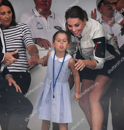 Britain's Princess Charlotte (C) sticks her tongue out to the crowd next to her mother, Catherine, Duchess of Cambridge (R) and her grandmother, Carole Middleton (L) during the King's Cup sailing regatta off the Isle of White, Britain, 08 August 2019. The Duke and Duchess of Cambridge took part in the race.