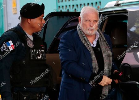 Panama's former President Ricardo Martinelli arrives at court, escorted by a police officer, to continue facing his trail for illegal wiretaps, in Panama City
