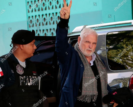 Stock Picture of Panama's former President Ricardo Martinelli flashes a victory sign as he arrives at court, escorted by a police officer, to continue facing his trail for illegal wiretaps, in Panama City
