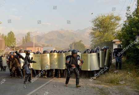 Kyrgyz riot police try to stop supporters of former president Almazbek Atambayev, near his residence in the village of Koi-Tash, about 20 kilometers (12 miles) south of the capital, Bishkek, Kyrgyzstan, . Police in Kyrgyzstan detained the Central Asian nation's ex-president Thursday following violent clashes with his supporters, a day after a previous attempt to arrest him left one policeman dead and nearly 80 people injured