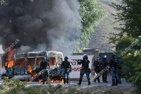 Kyrgyz riot police shoot rubber bullets to stop supporters of former president Almazbek Atambayev, near his residence in the village of Koi-Tash, about 20 kilometers (12 miles) south of the capital, Bishkek, Kyrgyzstan, . Police in Kyrgyzstan detained the Central Asian nation's ex-president Thursday following violent clashes with his supporters, a day after a previous attempt to arrest him left one policeman dead and nearly 80 people injured