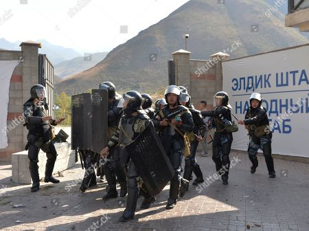 Kyrgyz riot police enter the residence of former president Almazbek Atambayev in the village of Koi-Tash, about 20 kilometers (12 miles) south of the capital, Bishkek, Kyrgyzstan, . Police in Kyrgyzstan detained the Central Asian nation's ex-president Thursday following violent clashes with his supporters, a day after a previous attempt to arrest him left one policeman dead and nearly 80 people injured