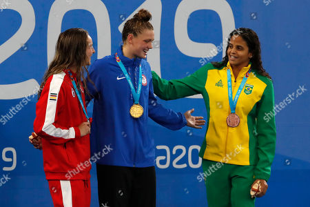 Bronze medalist Pires De Medeiros, right, congrats gold medalist Phoebe Bacon, center, next to silver medalist Danielle Hanus of Canada during the awards ceremony for the women's swimming 100m backstroke at the Pan American Games in Lima, Peru