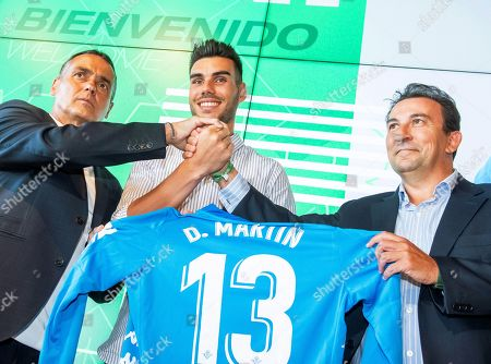 Real Betis' new Spanish goalkeeper Dani Martin (C) poses for photographers with Betis' CEO Jose Miguel Lopez Catalan (R) and Betis' technical secretary Alexis Trujillo (L) during his presentation as new player of the Spanish La Liga soccer club in Seville, Spain, 08 August 2019.