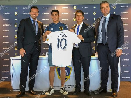 Chris Klein, Cristian Pavón, Guillermo Barros Schelotto, Dennis Te Kloese. Forward Cristian Pavón, second from left, of Argentina, holds up his new LA Galaxy jersey at Dignity Health Sports Park in Carson, Calif., . Standing alongside Pavon, Galaxy President Chris Klein, left, head coach Guillermo Barros Schelotto, second from right, and general manager Dennis te Kloese. The LA Galaxy acquired Pavón on loan from Argentina's Boca Juniors this week in one of the biggest player acquisitions in recent Major League Soccer history