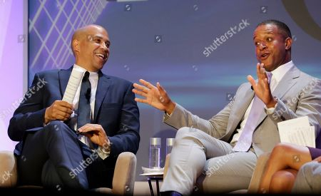 Cory Booker, Craig Melvin. Democratic Presidential candidate Sen. Cory Booker, D-N.J., left, smiles as moderator Craig Melvin speaks during the annual National Association of Black Journalists forum, in Aventura, Fla