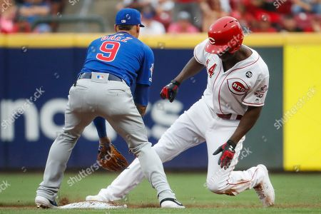 Aristides Aquino, Javier Baez. Cincinnati Reds' Aristides Aquino (44) slides in safely against Chicago Cubs shortstop Javier Baez (9) with an RBI double during the first inning of a baseball game, in Cincinnati