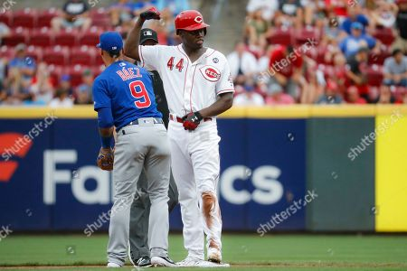 Aristides Aquino, Javier Baez. Cincinnati Reds' Aristides Aquino (44) celebrates after sliding in safely against Chicago Cubs shortstop Javier Baez (9) with an RBI double during the first inning of a baseball game, in Cincinnati