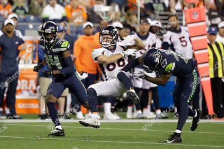 Seattle Seahawks defensive back Marquise Blair, right, hits Denver Broncos wide receiver Nick Williams, center, drawing a penalty flag for unnecessary roughness, as Seahawks defensive back Simeon Thomas, left, watches during the second half of an NFL football preseason game, in Seattle