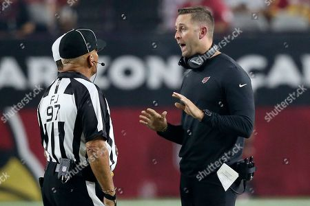 Arizona Cardinals head coach Kliff Kingsbury talks with field judge Tom Hill (97) during the first half of an NFL preseason football game against the Los Angeles Chargers, in Glendale, Ariz