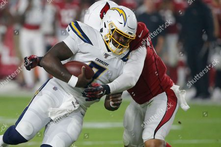 Los Angeles Chargers quarterback Cardale Jones, left, is hit by Arizona Cardinals linebacker Pete Robertson during the first half of an NFL preseason football game, in Glendale, Ariz