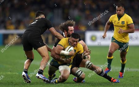 Tolu Latu of the Wallabies is tackled by Samuel Whitelock of the All Blacks