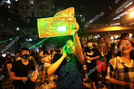 Anti-government protesters try to burn paper money with laser pointers to protest against the government and mark the Hungry Ghost Festival in Wong Tai Sin, Hong Kong, China, 09 August 2019. Hong Kong has been gripped for weeks by mass protests, which began in June 2019 over a now-suspended extradition bill to China and have developed into an anti-government movement. The Ghost Festival 2019 will start on 15 August.