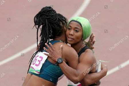 Gold medalist Shelly-Ann Fraser-Pryce of Jamaica is embraced by silver medalist Vitoria Cristina Silva of Brazil after the women's 200m final during the athletics at the Pan American Games in Lima, Peru