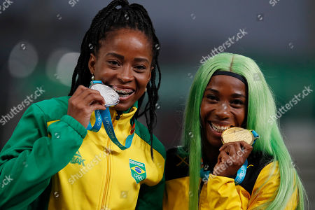 Silver medalist Vitoria Cristina Silva of Brazil, left, and gold medalist Shelly-Ann Fraser-Pryce of Jamaica celebrate at the podium for the women's 200m during the athletics at the Pan American Games in Lima, Peru