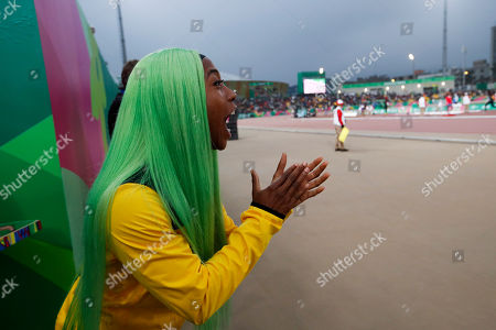 Shelly-Ann Fraser-Pryce of Jamaica, who won the gold medal in the women's 200m, cheers for teammate Aisha Praught while she runs to win the silver medal in the women's 1500m during the athletics at Pan American Games in Lima, Peru