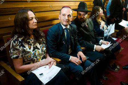 German Foreign Minister Heiko Maas, centre, sits between his partner Natalia Woerner, left, and Rabbi Yehuda Teichtal, third from left, as he arrives for solidarity prayer for tolerance, dialogue, against racism and anti-semitism at the synagogue of the Chabad Lubawitsch education center in Berlin, . German police have opened an investigation into a report from the Rabbi Yehuda Teichtal that he was insulted and spat at as he was heading home from synagogue with his son