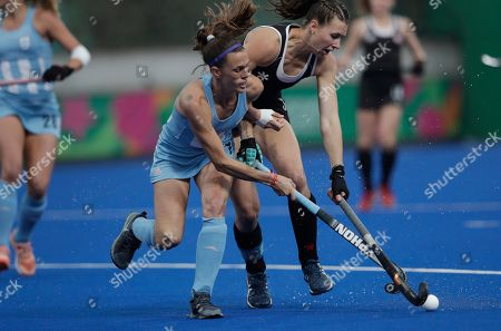 Carla Rebecchi of Argentina, left, fights for the ball with Canada's Katherine Wright during the women's field hockey gold medal match at the Pan American Games in Lima, Peru
