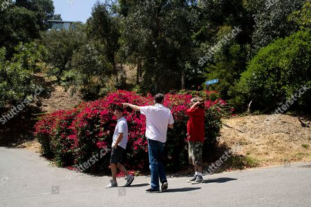 Stock Picture of People take picture of the entrance of the road leading to number 10050 of Cielo Drive where actress Sharon Tate was killed along with Abigail Folger, Wojciech Frykowski, Steven Parent and Jay Sebring by members of the 'Manson Family' under direction of Charles Manson on the night of August 08 1969, in Beverly Hills, California, USA, 09 August 2019. Today marks the 50th anniversary of the Tate Murders.