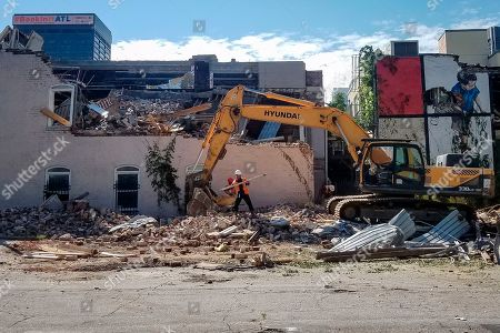 "Stock Photo of Building with country music legacy partially demolished. Demolition of a historic building is shown, in Atlanta. The building is the site where the first country hit song is believed to have been recorded. Soon after demolition began on Thursday, Aug. 8, 2019, a Fulton County court ordered the work stopped and issued a temporary restraining order. Fiddlin' John Carson likely recorded ""Little Log Cabin in the Lane"" in the building in 1923"
