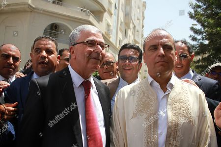 Tunisian Defence Minister Abdelkarim Zbidi (2-L) is surrounded by supporters after submitting his candidacy