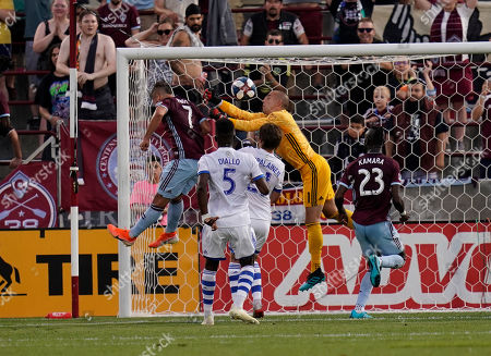 Diego Rubio, Evan Bush. Colorado Rapids forward Diego Rubio (7) scores a goal against Montreal Impact goalkeeper Evan Bush (1) as Montreal Impact defender Zakaria Diallo (5) and Colorado Rapids forward Kei Kamara (23) look on during the first half of an MLS soccer match, in Commerce City, Colo