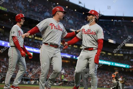 Bryce Harper, Rhys Hoskins, Drew Smyly. Philadelphia Phillies' Drew Smyly, Rhys Hoskins, and Bryce Harper, from left, celebrate after scoring on a triple by Corey Dickerson against the San Francisco Giants during the third inning of a baseball game, in San Francisco