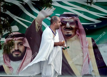 A Lebanese pilgrim walks in front of a banner showing Saudi King Salman, right, and his Crown Prince Mohammed bin Salman, near the Mountain of Mercy, on the Plain of Arafat, during the annual hajj pilgrimage, near the holy city of Mecca, Saudi Arabia, . More than 2 million pilgrims were gathered to perform initial rites of the hajj, an Islamic pilgrimage that takes the faithful along a path traversed by the Prophet Muhammad some 1,400 years ago