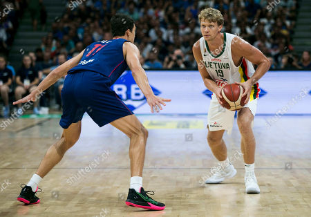Mindaugas Kuzminskas of Lithuania competes against Vladimir Lucic of Serbia