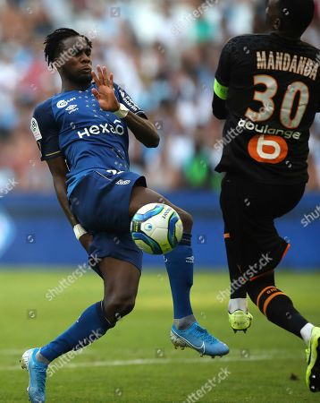 Reims' Boulaye Dia, left, is challenged by Marseille's goalkeeper Steve Mandanda during the French League One soccer match between Marseille and Reims at the Velodrome Stadium in Marseille, France