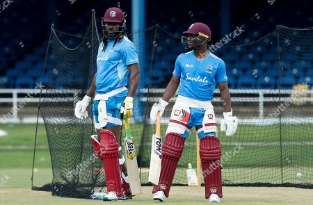 West Indies' Chris Gayle, left, and Evin Lewis talk during a training session ahead their second One-Day International cricket match against India in Port of Spain, Trinidad