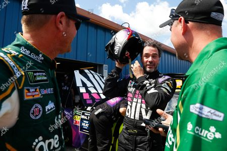 Jimmie Johnson, center, talks with Clint Bowyer, left, during practice for a NASCAR Cup Series auto race at Michigan International Speedway in Brooklyn, Mich