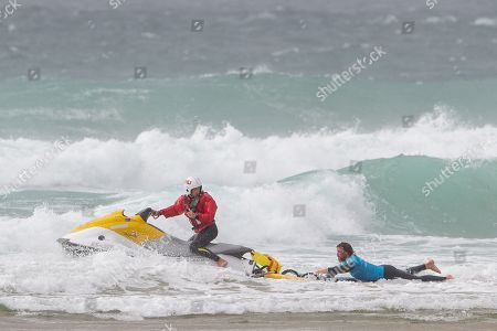 Stock Image of RNLI Lifeguard tows Ben Skinner away from the rocks during the Boardmasters Longboard Pro at Fistral Beach, Newquay, Cornwall