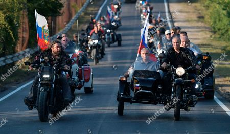 "Russian President Vladimir Putin drives a motorbike, right, as Head of motorcycle club ""Night Wolves"" Alexander Zaldostanov, left, follows him during the Babylon's Shadow bike show camp near in Sevastopol, Crimea, . Head of the Republic of Crimea Sergei Aksenov, is in sidecar, and acting Governor of Sevastopol Mikhail Razvozhaev, rides pillion"