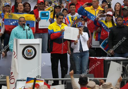 Venezuela's President Nicolas Maduro, center, and first lady wife Cilia Flores, show his signature on a document condemning the economic sanctions imposed by the administration of U.S. President Donald Trump on Veneuzela, in Caracas, Venezuela, Saturday, Aug. 10. 2019. Supporters of Maduro joined him after he called for protests against the fresh moves by the U.S. to tighten sanctions against the ruling authorities