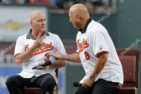 Former Baltimore Orioles infielder Billy Ripken, left, talks to his brother and teammate Cal Ripken, Jr. during a ceremony honoring the 1989 team prior to a baseball game against the Houston Astros, in Baltimore