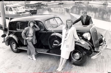 Duke And Duchess Of Windsor - Cars And Driving - 1987 Tv Actors From 'howards Way' Sarah-jane Varley (blonde Light Suit) Susan Gilmore (dark Hair) And Maurice Colbourne Seen With The Buick Car. It Is The Most Romantic Car Of The Century...the Luxurious 1936 Canadian-built Buick The Duke Of Windsor Bought To Please Wallis Simpson The Woman For Whom He Gave Up The Crown Of England. Ten Months Before He Abdicated King Edward Bought This Limousine. The Duke Had The Car Specially Designed To Keep The Romance With Mrs Simpson Secret. The Rear Window Narrows At The Back For Perfect Privacy; Side Windows Are Smaller And Darker So Rear-seat Passengers Are Virtually Invsible To The Outside World; There Is A Plush Drinks Cabinet In The Back And A Glass Partition Separates The Passangers From The Driver. Daily Mail Readers Will Soon Have The Chance To Win This Ultimate In Prestigious Vehicles Together With Its Log-book Bearing Details Of The King's Ownership. The Buick Was Bought At Sotheby's For More Than 130 000 And Still Carries Its Original Registration Cul 421. Picture Desk ** Pkt 940 - 63031