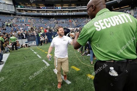Seattle Seahawks general manager John Schneider, center, greets a security worker before an NFL football preseason game against the Denver Broncos, in Seattle
