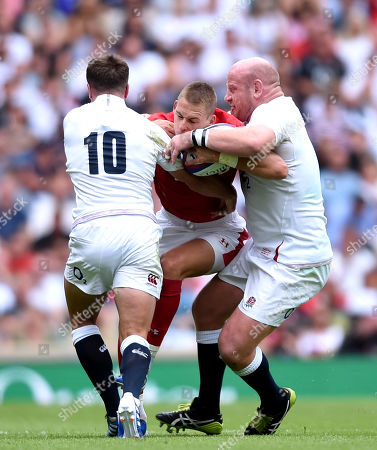 Liam Williams of Wales is tackled by George Ford and Dan Cole of England.