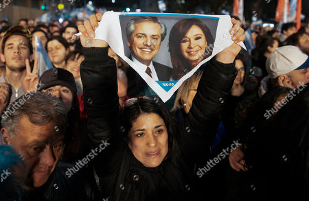 """A supporter of presidential candidate Alberto Fernandez holds up a handkerchief with photos of him and his running-mate, former President Cristina Fernandez, outside the """"Frente de Todos"""" party headquarters after primary elections in Buenos Aires, Argentina, . The """"Frente de Todos"""" presidential ticket emerged as the strongest vote-getter in Argentina's primary elections Sunday, indicating conservative President Mauricio Macri will face an uphill battle going into general elections in October"""