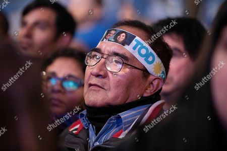 """A supporter of presidential candidate Alberto Fernandez with a headband decorated with photos of him and his running-mate, former President Cristina Fernandez, rallies outside the """"Frente de Todos"""" party headquarters after primary elections in Buenos Aires, Argentina, . The """"Frente de Todos"""" presidential ticket with former President Cristina Fernández emerged as the strongest vote-getter in Argentina's primary elections Sunday, indicating conservative President Mauricio Macri will face an uphill battle going into general elections in October"""