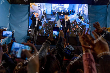 """Presidential candidate Alberto Fernandez, left, addresses supporters next to his partner Fabiola Yanez outside the """"Frente de Todos"""" party headquarters after primary elections in Buenos Aires, Argentina, . The """"Frente de Todos"""" presidential ticket with former President Cristina Fernández emerged as the strongest vote-getter in Argentina's primary elections Sunday, indicating conservative President Mauricio Macri will face an uphill battle going into general elections in October"""