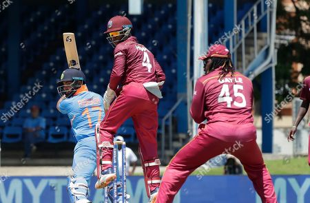 India Rishabh Pant, left, bats as West Indies wicketkeeper Shai Hope, center, and Chris Gayle, right, look on during their second One-Day International cricket match in Port of Spain, Trinidad