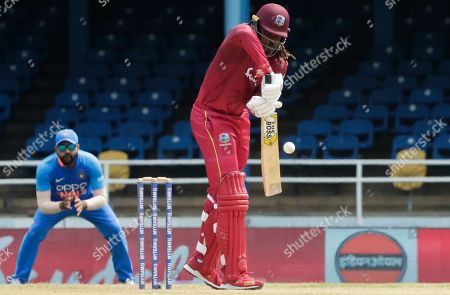 West Indies opening batsman Chris Gayle defends his wicket during the second One-Day International cricket match against India in Port of Spain, Trinidad