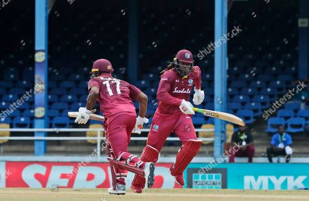West Indies opening batsmen Evin Lewis, left, and Chris Gayle run between the wickets during the second One-Day International cricket match against India in Port of Spain, Trinidad