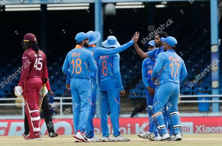 India's bowler Bhuvneshwar Kumar, second right, is congratulated by teammates after taking the wicket of West Indies' Chris Gayle, left, who was trapped LBW for a 11 runs, during their second One-Day International cricket match in Port of Spain, Trinidad