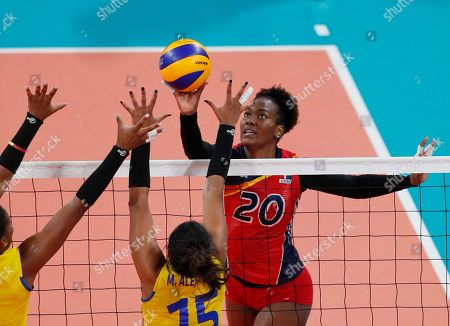 Stock Image of Elizabeth Martinez of the Dominican Republic, right, gets past a block by Colombia's Maria Marin, center and Colombia's Valerin Carabali in their gold medal volleyball game at the Pan American Games in Lima, Peru