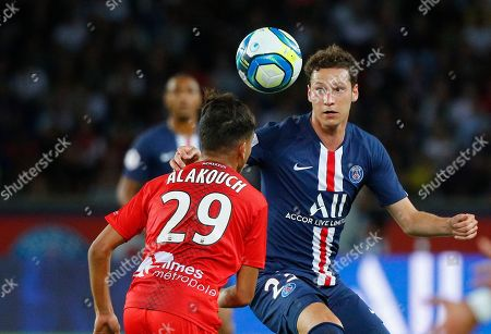 PSG's Julian Draxler, right, challenges for the ball with Nimes' Sofiane Alakouch during the French League One soccer match between Paris Saint Germain and Nimes at the Parc des Princes Stadium in Paris