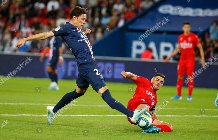 PSG's Julian Draxler, left, challenges for the ball with Nimes' Anthony Briancon during the French League One soccer match between Paris Saint Germain and Nimes at the Parc des Princes Stadium in Paris