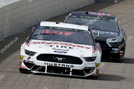 Brad Keselowski leads Kevin Harvick into turn one during a NASCAR Cup Series auto race at Michigan International Speedway in Brooklyn, Mich